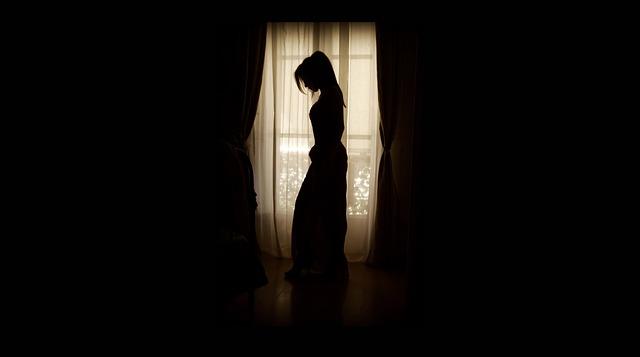 dívka stojí u okna